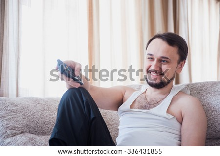 bearded man is watching TV and smiling