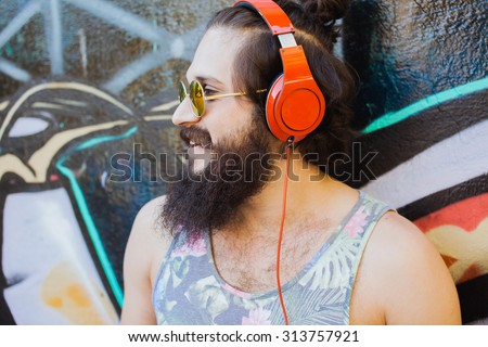 Bearded man,lifestyle portrait of hipster man,cool beard hairstyle.mans haircut.Stylish man posing with cool hairstyle,wall,ready to car trip.Happy and active,Young sportsman,California east coast - stock photo