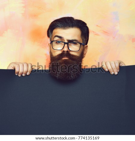 Bearded man, long beard. Brutal caucasian unshaven serious hipster with glasses and moustache holding blue paper sheet on colorful studio background