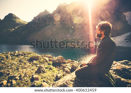 Bearded Man meditating relaxing alone Travel healthy Lifestyle concept lake and mountains sunny landscape on background outdoor  - stock photo