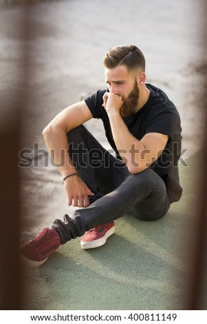 Bearded man posing in the street.