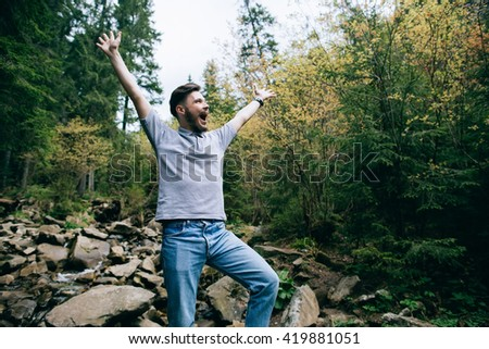 Bearded man raised his hands up in mountain forest. Hiker crosses a river at the ford - stock photo