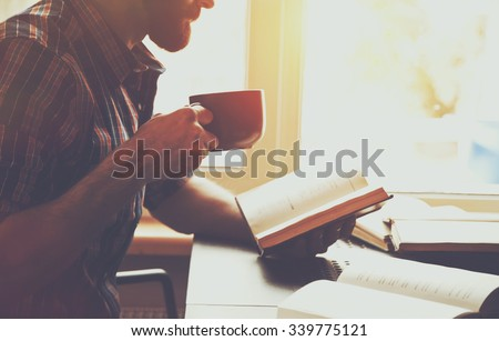 bearded man reading book with coffee or tea - stock photo