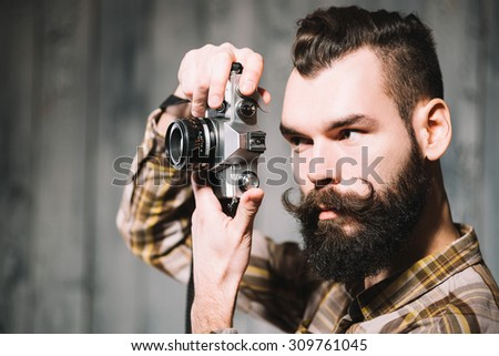 Bearded man shoots with a vintage film camera. - stock photo