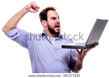 Bearded man shouting angrily at his laptop and waving his fist - stock photo
