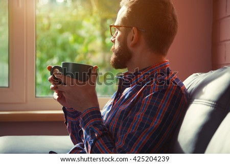 bearded man sitting with cup of morning coffee or tea and looking at window - stock photo