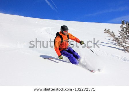 Bearded man skiing powder on a bluebird day in the Utah mountains, USA. - stock photo