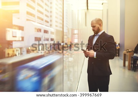 Bearded man skilled managing director is searching on web site via mobile phone needed information for meeting with clients, while is standing near window with view of the main street of New York - stock photo