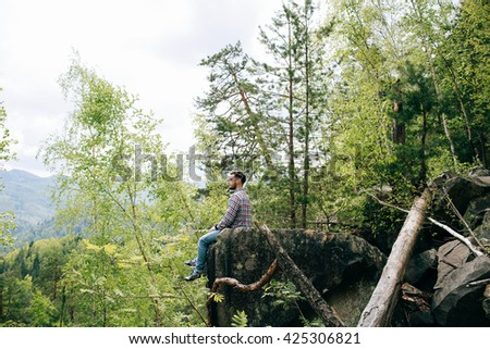 bearded man tourist hipster sits on rock and dream in mountain green forest