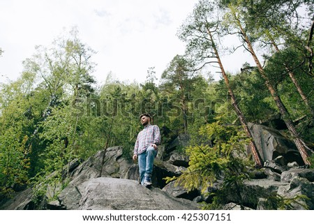 bearded man tourist hipster stands on rock and dream in mountain green forest