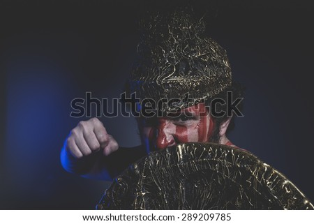 bearded man warrior with metal helmet and shield, wild Viking - stock photo