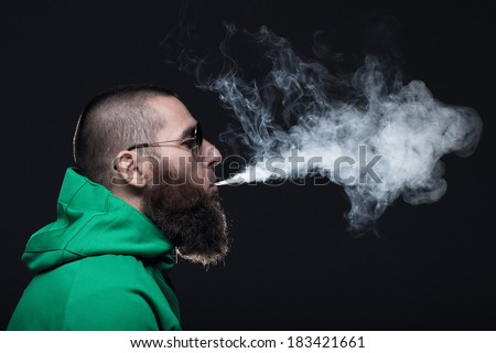 Bearded man, wearing a green sweatshirt and sunglasses, smoking - stock photo