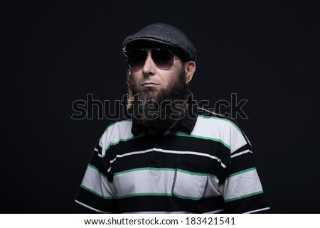 Bearded man, wearing a hat and sunglasses - stock photo