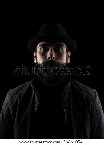 Bearded man wearing black hat looking at camera. Low key dark shadow portrait isolated over black background. - stock photo