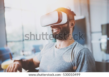 Bearded man wearing virtual reality glasses in modern interior design coworking studio. Smartphone using with VR goggles headset. Horizontal,film effect, blurred background