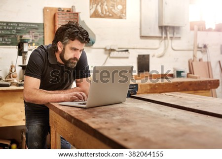 Bearded man who owns a small business, bending over at his work bench to type on his laptop, while working in his workshop and design studio - stock photo