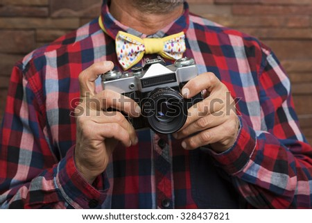 Bearded man with a bow tie holding a camera - stock photo