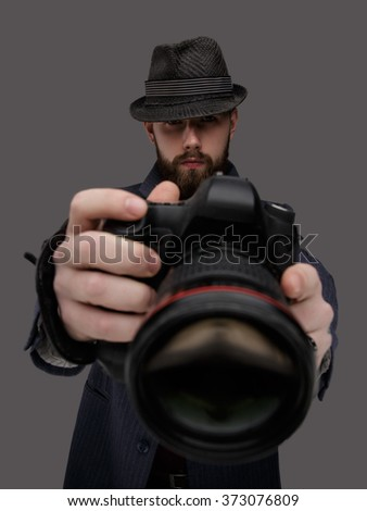 Bearded man with a dslr camera. Isolated on a grey background. - stock photo