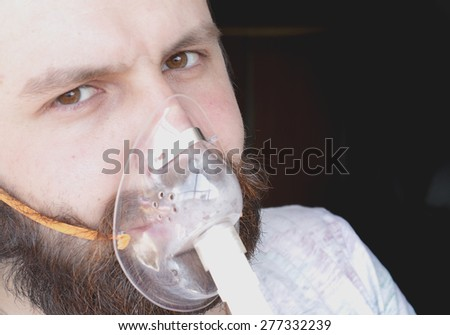 bearded man with an asthma inhaler to breathe health - stock photo