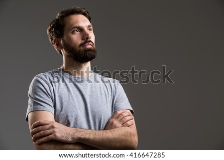 Bearded man with crossed arms on grey background