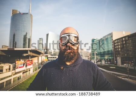 bearded man with glasses aviator in the high city  - stock photo