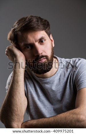 Bearded man with head leaning on hand on dark grey background