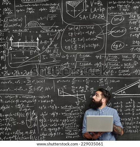 Bearded man with laptop looking at chalkboard with formulas - stock photo
