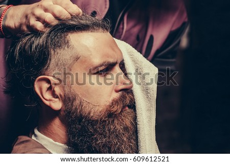 Bearded man with long beard, brutal, caucasian hipster with moustache, getting stylish hair haircut with towel by barber or hairdresser hands at barbershop