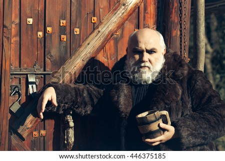 bearded man with long beard on serious face holding wood cup with iron decoration in fur coat outdoor on wooden background