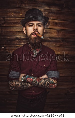 Bearded man with tattooes on arms smoking cigar. - stock photo