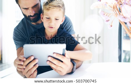 Bearded man with young boy using tablet PC in sunny room.Dad and little son playing together on mobile computer, resting indoor.Horizontal, blurred background