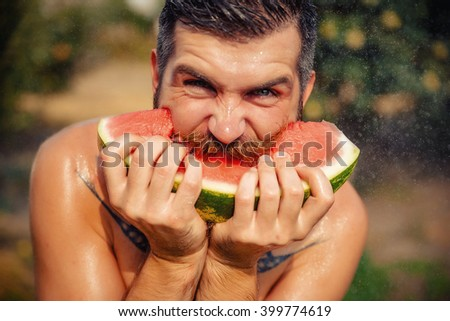 bearded man without clothes with a big juicy ripe watermelon in hands on a background of flowering garden illuminated by bright sunshine - stock photo