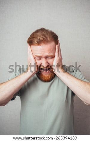 bearded man yells, holding his head - stock photo