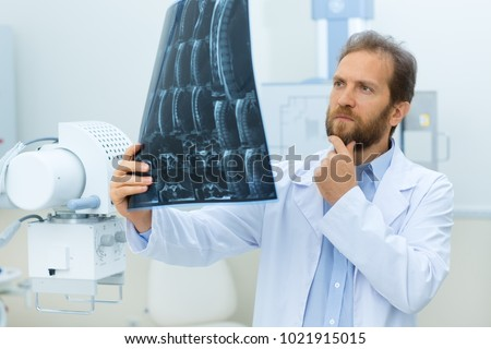 Bearded mature male doctor looking confused exmining x-ray scan at the hospital profession occupation job people healthcare medicine MRI technology modern survey science biology chemistry concept