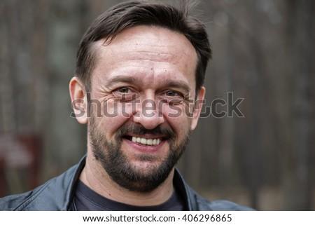 Bearded mature man in the demi-season jacket. Street photography - stock photo