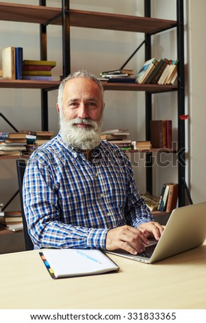 bearded middle-aged man with laptop in office looking at camera and smiling - stock photo