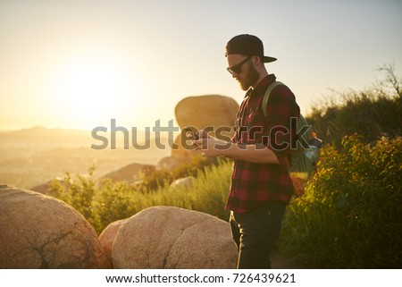 bearded millennial hiker using smartphone during hike