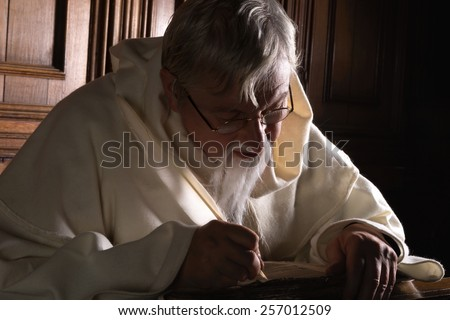 Bearded monk writing with a quill in a dark church - stock photo