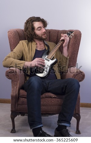 Bearded musician playing electric ukulele guitar in vintage chair - stock photo