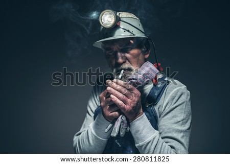 Bearded Old Male Miner Lighting his Cigarette on his Mouth While Holding his Gloves and Looking at the Camera Against Gray Gradient Background.