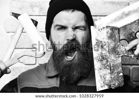 bearded painter man, long beard, brutal caucasian hipster with moustache in uniform holding various building tools: hammer, roller paint and spatulas with satisfied face, brick wall studio background