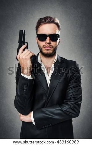 Bearded secret agent wearing a dark suit and sunglasses holding a handgun - stock photo