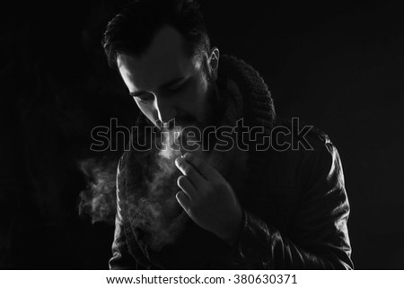 bearded stylish man holding and smoking electronic cigarette