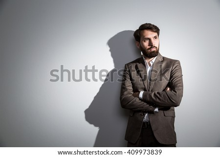 Bearded usinessman in suit standing against wall with shadow. Mock up