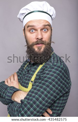 Bearded young chef with surprised expression over gray background - stock photo