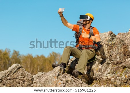 Bearded young man, makes selfie, in glasses virtual reality, outdoors the mountains