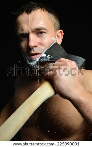 Bearded young man shaving with big axe foam and water splashes on a black background - stock photo
