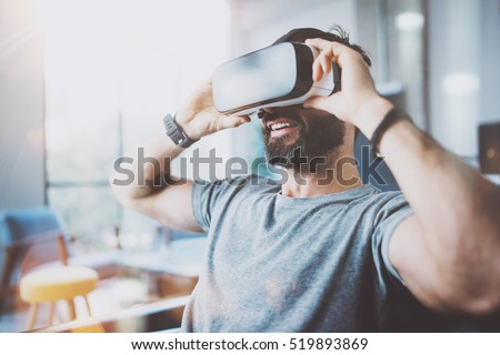 Bearded young man wearing virtual reality goggles in modern coworking studio. Smartphone using with VR headset in office. Horizontal, blurred