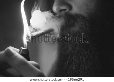 beareded man lighting up joint, cigarette, black and white - stock photo