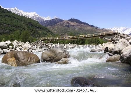 Beas river with wooden bridge in the Kullu valley near Manali. - stock photo